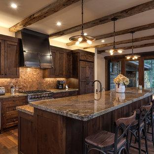 Foto di una cucina stile rurale con ante in stile shaker, ante in legno bruno, paraspruzzi marrone, paraspruzzi con piastrelle a mosaico, elettrodomestici da incasso, parquet scuro e isola