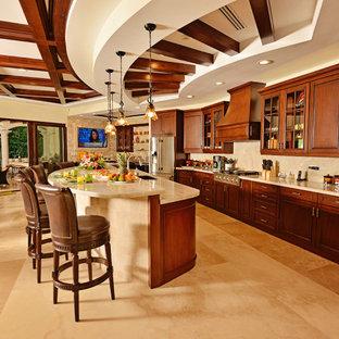他の地域のトロピカルスタイルのおしゃれなキッチン (アンダーカウンターシンク、落し込みパネル扉のキャビネット、濃色木目調キャビネット、ベージュキッチンパネル、石スラブのキッチンパネル、シルバーの調理設備、茶色い床、ベージュのキッチンカウンター、表し梁) の写真
