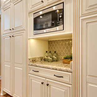 Photo of a mid-sized traditional u-shaped eat-in kitchen in Atlanta with an undermount sink, raised-panel cabinets, granite benchtops, beige splashback, stainless steel appliances, light hardwood floors, with island, beige cabinets, porcelain splashback, brown floor and beige benchtop.