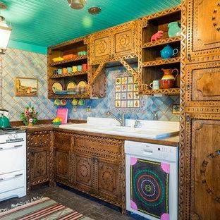 アルバカーキのサンタフェスタイルのおしゃれなコの字型キッチン (ダブルシンク、中間色木目調キャビネット、マルチカラーのキッチンパネル、白い調理設備、アイランドなし、セラミックタイルのキッチンパネル) の写真