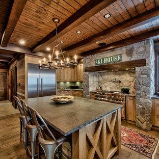 Ispirazione per una grande cucina a L rustica con ante con riquadro incassato, ante in legno chiaro, top in cemento, elettrodomestici in acciaio inossidabile, isola, pavimento in legno massello medio e paraspruzzi verde