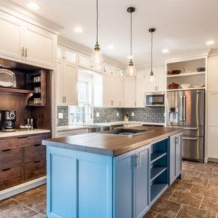 フィラデルフィアの中くらいのカントリー風おしゃれなキッチン (エプロンフロントシンク、フラットパネル扉のキャビネット、白いキャビネット、木材カウンター、グレーのキッチンパネル、セラミックタイルのキッチンパネル、シルバーの調理設備、クッションフロア、茶色い床、茶色いキッチンカウンター) の写真