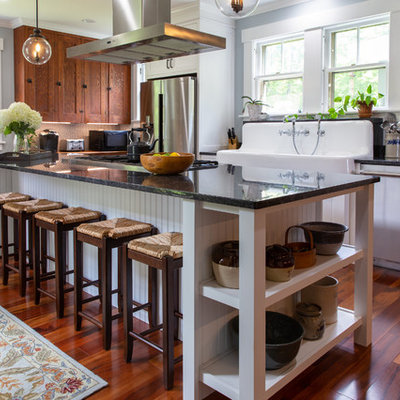 Inspiration for a country l-shaped medium tone wood floor and brown floor kitchen remodel in Boston with a farmhouse sink, recessed-panel cabinets, medium tone wood cabinets, stainless steel appliances and black countertops