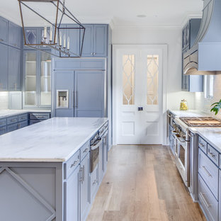 На фото: кухни в классическом стиле с фасадами в стиле шейкер, фиолетовыми фасадами, техникой под мебельный фасад, светлым паркетным полом, островом, бежевым полом и белой столешницей