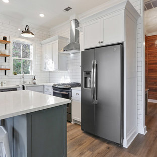 This is an example of a small transitional l-shaped eat-in kitchen in New Orleans with an undermount sink, shaker cabinets, white cabinets, quartz benchtops, white splashback, subway tile splashback, stainless steel appliances, vinyl floors and with island.