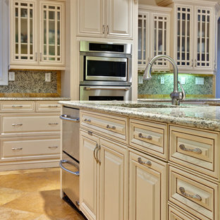 This is an example of an expansive traditional l-shaped eat-in kitchen in Atlanta with raised-panel cabinets, beige cabinets, stainless steel appliances, an undermount sink, granite benchtops, multi-coloured splashback, travertine floors, with island, orange floor and beige benchtop.