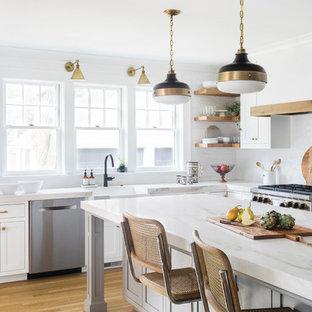 Idéer för stora lantliga kök, med en rustik diskho, skåp i shakerstil, vita skåp, vitt stänkskydd, rostfria vitvaror, mellanmörkt trägolv, en köksö, brunt golv och stänkskydd i cementkakel