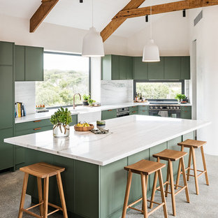Foto på ett stort funkis vit kök, med en rustik diskho, gröna skåp, marmorbänkskiva, vitt stänkskydd, stänkskydd i marmor, svarta vitvaror, betonggolv, en köksö, grått golv och släta luckor