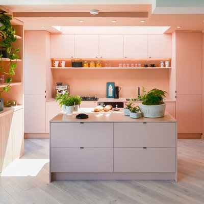 Example of a mid-sized minimalist single-wall gray floor and light wood floor kitchen design in London with an undermount sink, flat-panel cabinets, pink backsplash, black appliances and an island