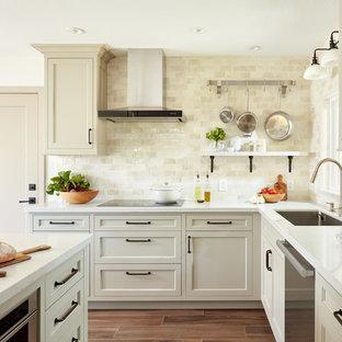 Immagine di una cucina a L classica con lavello sottopiano, ante con riquadro incassato, ante beige, paraspruzzi beige, elettrodomestici in acciaio inossidabile, isola, pavimento marrone e top bianco