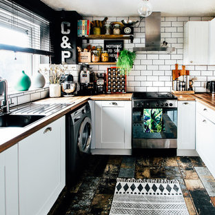 Inspiration for a small eclectic u-shaped enclosed kitchen in Cardiff with a single-bowl sink, shaker cabinets, white cabinets, laminate countertops, white splashback, ceramic splashback, stainless steel appliances, multi-coloured floors and brown worktops.