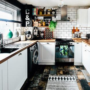 カーディフの小さいエクレクティックスタイルのおしゃれなキッチン (シングルシンク、シェーカースタイル扉のキャビネット、白いキャビネット、ラミネートカウンター、白いキッチンパネル、セラミックタイルのキッチンパネル、シルバーの調理設備の、マルチカラーの床、茶色いキッチンカウンター) の写真