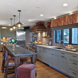 На фото: угловая кухня среднего размера в стиле неоклассика (современная классика) с врезной раковиной, техникой из нержавеющей стали, обеденным столом, фасадами с утопленной филенкой, серыми фасадами, столешницей из кварцевого агломерата, островом, красным фартуком и паркетным полом среднего тона