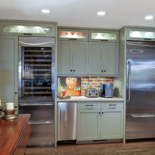 Photo of a transitional kitchen in Charleston with shaker cabinets, red splashback, stainless steel appliances and green cabinets.