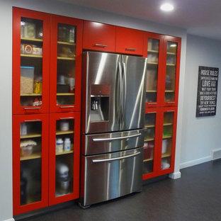 ボストンの巨大なコンテンポラリースタイルのおしゃれなキッチン (フラットパネル扉のキャビネット、赤いキャビネット、シルバーの調理設備の、リノリウムの床、黒い床) の写真