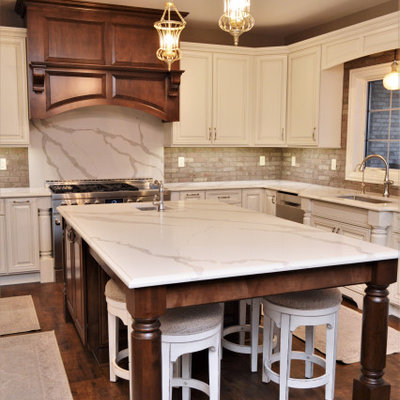 Huge elegant u-shaped medium tone wood floor and brown floor eat-in kitchen photo in Chicago with an undermount sink, raised-panel cabinets, white cabinets, quartzite countertops, gray backsplash, brick backsplash, stainless steel appliances, an island and white countertops