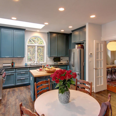 Eclectic u-shaped eat-in kitchen photo in DC Metro with recessed-panel cabinets, blue cabinets, white backsplash, subway tile backsplash and stainless steel appliances