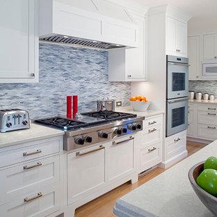 Mittelgroße Landhausstil Wohnküche in U-Form mit Unterbauwaschbecken, Schrankfronten im Shaker-Stil, weißen Schränken, Marmor-Arbeitsplatte, Küchenrückwand in Blau, Rückwand aus Marmor, Küchengeräten aus Edelstahl, hellem Holzboden, Kücheninsel und braunem Boden in Boston