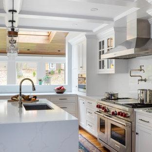 Bild på ett stort vintage gul gult l-kök, med en enkel diskho, luckor med infälld panel, vita skåp, marmorbänkskiva, vitt stänkskydd, stänkskydd i marmor, rostfria vitvaror, mellanmörkt trägolv och en köksö