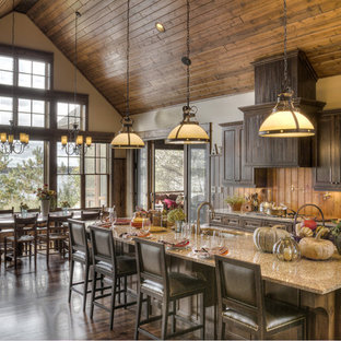 Photo of a large country galley eat-in kitchen in Minneapolis with an undermount sink, raised-panel cabinets, brown cabinets, granite benchtops, brown splashback, timber splashback, stainless steel appliances, dark hardwood floors, with island and brown floor.