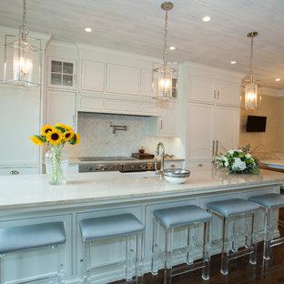 Источник вдохновения для домашнего уюта: большая параллельная кухня в классическом стиле с обеденным столом, раковиной в стиле кантри, фасадами с декоративным кантом, белыми фасадами, столешницей из известняка, белым фартуком, фартуком из удлиненной плитки, белой техникой, темным паркетным полом и островом