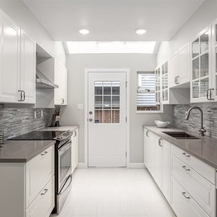 This is an example of a mid-sized contemporary galley separate kitchen in Vancouver with an undermount sink, raised-panel cabinets, white cabinets, solid surface benchtops, grey splashback, glass tile splashback, stainless steel appliances, ceramic floors, no island and white floor.