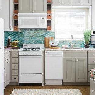 Inredning av ett maritimt litet grå grått kök, med en undermonterad diskho, skåp i shakerstil, grå skåp, granitbänkskiva, blått stänkskydd, vita vitvaror, vinylgolv, stänkskydd i glaskakel och brunt golv