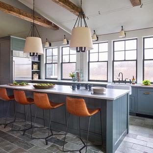 ボストンの中サイズのトランジショナルスタイルのおしゃれなキッチン (エプロンフロントシンク、シェーカースタイル扉のキャビネット、青いキャビネット、珪岩カウンター、白いキッチンパネル、サブウェイタイルのキッチンパネル、シルバーの調理設備の、スレートの床、グレーの床、白いキッチンカウンター) の写真