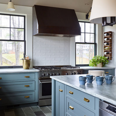 Inspiration for a mid-sized transitional l-shaped slate floor and gray floor enclosed kitchen remodel in Boston with a farmhouse sink, shaker cabinets, blue cabinets, quartzite countertops, white backsplash, subway tile backsplash, stainless steel appliances, an island and white countertops