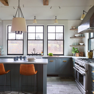 Enclosed kitchen - mid-sized transitional l-shaped slate floor and gray floor enclosed kitchen idea in Boston with a farmhouse sink, shaker cabinets, blue cabinets, quartzite countertops, white backsplash, subway tile backsplash, stainless steel appliances, an island and white countertops
