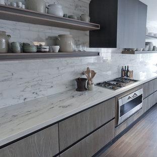 ロンドンの大きい地中海スタイルのおしゃれなキッチン (ドロップインシンク、フラットパネル扉のキャビネット、淡色木目調キャビネット、大理石カウンター、無垢フローリング) の写真