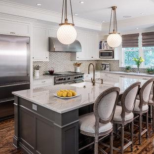 Foto de cocina en L, tradicional, con armarios estilo shaker, puertas de armario blancas, electrodomésticos de acero inoxidable y una isla