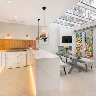 Photo of a contemporary u-shaped kitchen/diner in London with a double-bowl sink, flat-panel cabinets, white cabinets, engineered stone countertops, white appliances, porcelain flooring, a breakfast bar, beige floors, white worktops, metallic splashback and metal splashback.