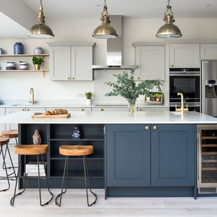 This is an example of a large traditional kitchen in London with shaker cabinets, quartz worktops, an island, a submerged sink, grey cabinets, stainless steel appliances, light hardwood flooring and white worktops.