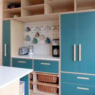 ロンドンの広い北欧スタイルのおしゃれなキッチン (ダブルシンク、フラットパネル扉のキャビネット、ターコイズのキャビネット、白いキッチンパネル、セラミックタイルのキッチンパネル、シルバーの調理設備、無垢フローリング、茶色い床、白いキッチンカウンター) の写真
