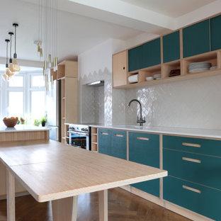 ロンドンの広いコンテンポラリースタイルのおしゃれなキッチン (ダブルシンク、フラットパネル扉のキャビネット、ターコイズのキャビネット、白いキッチンパネル、セラミックタイルのキッチンパネル、シルバーの調理設備、無垢フローリング、茶色い床、白いキッチンカウンター) の写真