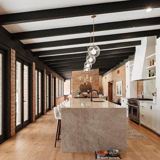 フェニックスのサンタフェスタイルのおしゃれなキッチン (シェーカースタイル扉のキャビネット、白いキャビネット、御影石カウンター、パネルと同色の調理設備、無垢フローリング、グレーのキッチンカウンター) の写真
