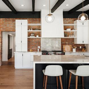 Offene Mediterrane Küche mit Schrankfronten im Shaker-Stil, weißen Schränken, Granit-Arbeitsplatte, Elektrogeräten mit Frontblende, braunem Holzboden, Kücheninsel, grauer Arbeitsplatte, Unterbauwaschbecken, Küchenrückwand in Rot, Rückwand aus Backstein und braunem Boden in Phoenix