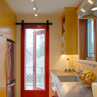 Contemporary enclosed kitchen designs - Inspiration for a contemporary galley enclosed kitchen remodel in Other with stainless steel appliances, an integrated sink, yellow cabinets, stainless steel countertops, yellow backsplash and flat-panel cabinets