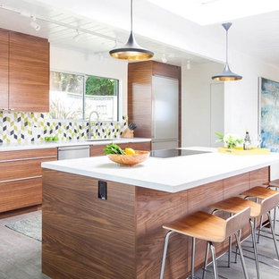 Mid-sized midcentury galley open plan kitchen in San Francisco with an undermount sink, flat-panel cabinets, medium wood cabinets, quartz benchtops, multi-coloured splashback, ceramic splashback, stainless steel appliances, ceramic floors, with island and grey floor.
