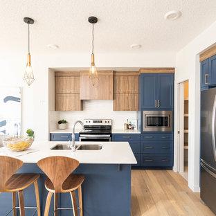 Cette image montre une cuisine américaine marine avec un évier 2 bacs, un placard à porte shaker, des portes de placard bleues, une crédence blanche, un électroménager en acier inoxydable, un sol en bois clair, un îlot central, un sol beige et un plan de travail blanc.