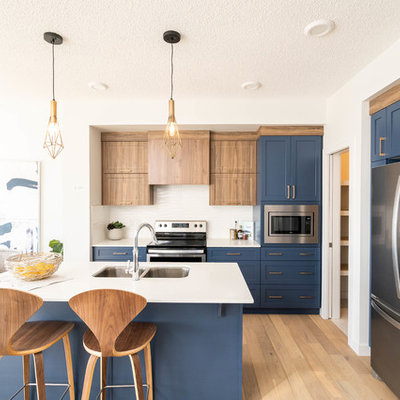 Example of a small trendy l-shaped light wood floor and beige floor open concept kitchen design in Edmonton with shaker cabinets, blue cabinets, white backsplash, stainless steel appliances, an island, white countertops, an undermount sink, marble countertops and ceramic backsplash