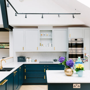 Design ideas for a medium sized contemporary l-shaped kitchen in London with a double-bowl sink, marble worktops, white splashback, marble splashback, stainless steel appliances, an island and beige floors.