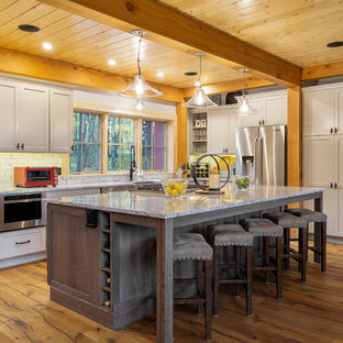 Inspiration for a large rustic l-shaped open plan kitchen in Boston with a belfast sink, shaker cabinets, granite worktops, white splashback, stainless steel appliances, medium hardwood flooring, an island, grey cabinets, brown floors and multicoloured worktops.