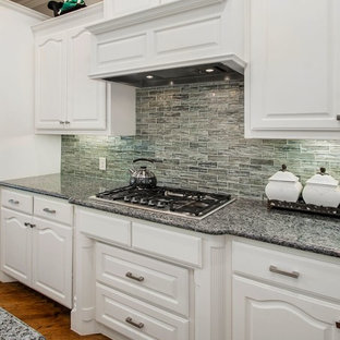 Inspiration for a medium sized traditional u-shaped kitchen pantry in Dallas with a submerged sink, raised-panel cabinets, white cabinets, engineered stone countertops, metallic splashback, glass tiled splashback, black appliances, medium hardwood flooring, an island, brown floors and grey worktops.