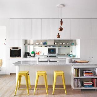 Mid-sized trendy galley light wood floor eat-in kitchen photo in Sydney with an undermount sink, white cabinets, marble countertops, mirror backsplash, stainless steel appliances and an island