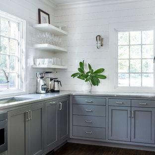 Maritime Küche in L-Form mit Unterbauwaschbecken, Schrankfronten mit vertiefter Füllung, grauen Schränken, Küchenrückwand in Weiß, Küchengeräten aus Edelstahl, dunklem Holzboden, braunem Boden und grauer Arbeitsplatte in Atlanta