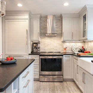 Inspiration for a mid-sized transitional l-shaped kitchen in Bridgeport with a farmhouse sink, recessed-panel cabinets, grey cabinets, granite benchtops, grey splashback, ceramic splashback, stainless steel appliances, vinyl floors, black benchtop and beige floor.