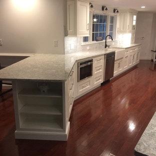 ボストンの大きいトラディショナルスタイルのおしゃれなキッチン (エプロンフロントシンク、インセット扉のキャビネット、白いキャビネット、クオーツストーンカウンター、グレーのキッチンパネル、石タイルのキッチンパネル、シルバーの調理設備の、濃色無垢フローリング、赤い床) の写真