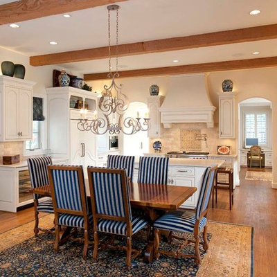 Elegant u-shaped eat-in kitchen photo in Dallas with a farmhouse sink, raised-panel cabinets, white cabinets, beige backsplash and paneled appliances